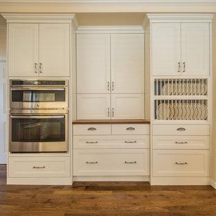 ウィチタの巨大なトラディショナルスタイルのおしゃれなキッチン (フラットパネル扉のキャビネット、ベージュのキャビネット、無垢フローリング、アイランドなし、木材カウンター、シルバーの調理設備) の写真