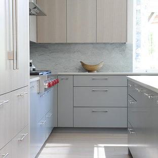 Esempio di una cucina minimal con lavello sottopiano, ante lisce, ante grigie, top in quarzo composito, paraspruzzi verde, paraspruzzi in lastra di pietra, parquet chiaro e isola