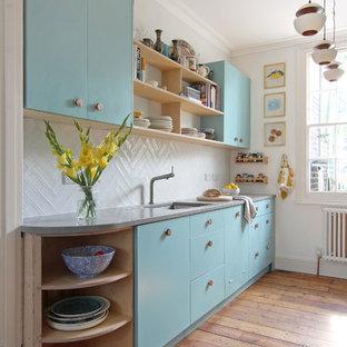 Idéer för små skandinaviska linjära kök, med en undermonterad diskho, släta luckor, blå skåp, vitt stänkskydd, mellanmörkt trägolv och bänkskiva i betong