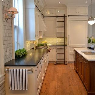 Inspiration för mellanstora klassiska u-kök, med en undermonterad diskho, luckor med infälld panel, vita skåp, bänkskiva i koppar, vitt stänkskydd, stänkskydd i tunnelbanekakel, integrerade vitvaror, mellanmörkt trägolv och en köksö
