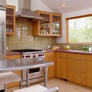 Immagine di una cucina a L minimalista con ante di vetro, ante in legno scuro, top in cemento, paraspruzzi giallo, paraspruzzi con piastrelle di vetro e elettrodomestici in acciaio inossidabile