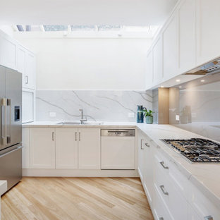 Photo of a mid-sized transitional l-shaped kitchen in Sydney with a drop-in sink, shaker cabinets, white cabinets, grey splashback, glass sheet splashback, stainless steel appliances, beige floor and grey benchtop.
