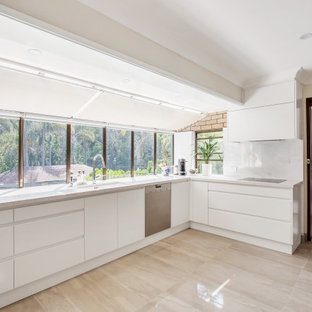 This is an example of a contemporary l-shaped kitchen in Newcastle - Maitland with an undermount sink, flat-panel cabinets, white cabinets, stainless steel appliances, no island, beige floor and white benchtop.