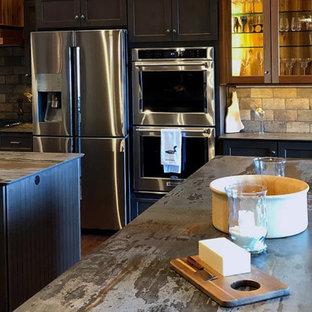 Große Rustikale Wohnküche in U-Form mit Unterbauwaschbecken, Schrankfronten mit vertiefter Füllung, grauen Schränken, Speckstein-Arbeitsplatte, Küchenrückwand in Beige, Rückwand aus Travertin, Küchengeräten aus Edelstahl, dunklem Holzboden, zwei Kücheninseln, braunem Boden und schwarzer Arbeitsplatte in Boston