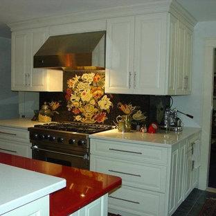На фото: параллельная кухня-гостиная среднего размера в классическом стиле с врезной раковиной, фасадами с выступающей филенкой, белыми фасадами, столешницей из кварцевого композита, черным фартуком, фартуком из плитки мозаики, техникой из нержавеющей стали, полом из сланца, островом и красной столешницей с