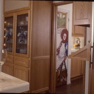 Réalisation d'une grand cuisine américaine bohème en U avec un évier 3 bacs, un placard à porte shaker, des portes de placard en bois clair, un plan de travail en carrelage, une crédence blanche, une crédence en carreau de céramique, un électroménager en acier inoxydable et un sol en bois brun.