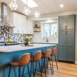 Design ideas for a mid-sized midcentury l-shaped eat-in kitchen with an undermount sink, shaker cabinets, blue cabinets, quartz benchtops, multi-coloured splashback, ceramic splashback, stainless steel appliances, vinyl floors, with island, brown floor and white benchtop.