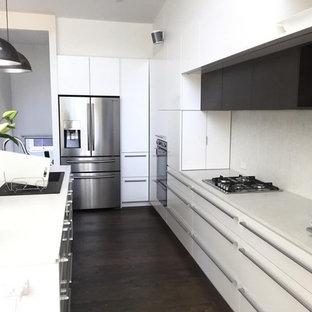 シドニーの広いモダンスタイルのおしゃれなキッチン (シングルシンク、白いキャビネット、大理石カウンター、白いキッチンパネル、石スラブのキッチンパネル、シルバーの調理設備、濃色無垢フローリング、白いキッチンカウンター) の写真