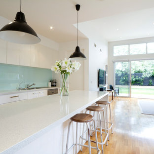 Inspiration for a contemporary single-wall open plan kitchen in Sussex with flat-panel cabinets, white cabinets, blue splashback, medium hardwood flooring, an island, brown floors and white worktops.
