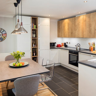 This is an example of a mid-sized contemporary u-shaped open plan kitchen in Dublin with an integrated sink, flat-panel cabinets, light wood cabinets, laminate benchtops, white splashback, ceramic splashback, stainless steel appliances, ceramic floors and no island.