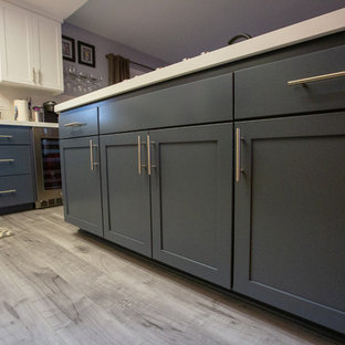 Example of a large minimalist eat-in kitchen design in Sacramento with an undermount sink, gray cabinets, quartz countertops, white backsplash, porcelain backsplash, stainless steel appliances, an island and gray countertops