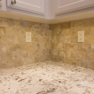 サクラメントのモダンスタイルのおしゃれなアイランドキッチン (アンダーカウンターシンク、白いキャビネット、クオーツストーンカウンター、ベージュキッチンパネル、トラバーチンの床、シルバーの調理設備の) の写真