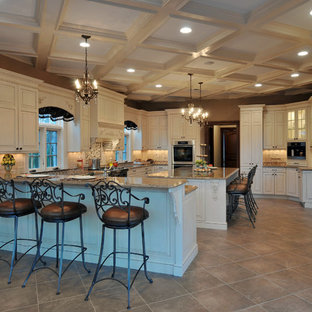 Huge elegant u-shaped ceramic floor eat-in kitchen photo in New York with raised-panel cabinets, white cabinets, granite countertops, beige backsplash, stone tile backsplash, stainless steel appliances, an island and an undermount sink