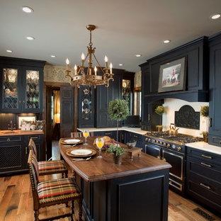 Aménagement d'une cuisine victorienne avec des portes de placard noires, un plan de travail en bois, une crédence beige et un électroménager noir.