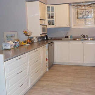 Photo of a mid-sized modern u-shaped separate kitchen in Toronto with a double-bowl sink, shaker cabinets, white cabinets, laminate benchtops, stainless steel appliances, vinyl floors and a peninsula.