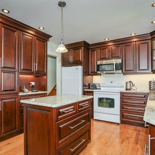 This is an example of a mid-sized traditional u-shaped eat-in kitchen in Toronto with a double-bowl sink, raised-panel cabinets, medium wood cabinets, quartzite benchtops, light hardwood floors and with island.