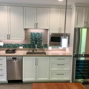 サンフランシスコの小さいトランジショナルスタイルのおしゃれなキッチン (シングルシンク、落し込みパネル扉のキャビネット、白いキャビネット、クオーツストーンカウンター、マルチカラーのキッチンパネル、ガラスタイルのキッチンパネル、シルバーの調理設備、クッションフロア、アイランドなし、グレーの床、ベージュのキッチンカウンター) の写真