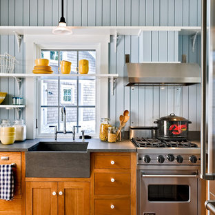 This is an example of a beach style kitchen in Portland Maine with stainless steel appliances, a farmhouse sink, shaker cabinets, medium wood cabinets and multi-coloured splashback.