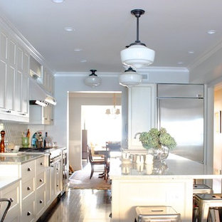 Traditional kitchen appliance - Elegant kitchen photo in Chicago with stainless steel appliances, shaker cabinets, white cabinets, white backsplash, subway tile backsplash and granite countertops