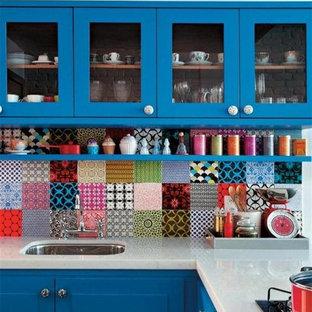 ミルウォーキーの中くらいのエクレクティックスタイルのおしゃれなキッチン (アンダーカウンターシンク、シェーカースタイル扉のキャビネット、青いキャビネット、人工大理石カウンター、マルチカラーのキッチンパネル、セラミックタイルのキッチンパネル) の写真