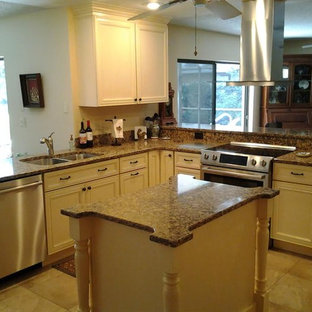 Mid-sized traditional open concept kitchen ideas - Open concept kitchen - mid-sized traditional l-shaped ceramic tile and brown floor open concept kitchen idea in Tampa with a double-bowl sink, recessed-panel cabinets, white cabinets, granite countertops and an island