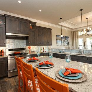 Mittelgroße Kolonialstil Wohnküche in L-Form mit Unterbauwaschbecken, Kassettenfronten, grauen Schränken, Granit-Arbeitsplatte, Küchenrückwand in Blau, Rückwand aus Glasfliesen, Küchengeräten aus Edelstahl, Porzellan-Bodenfliesen, Kücheninsel und buntem Boden in Orlando