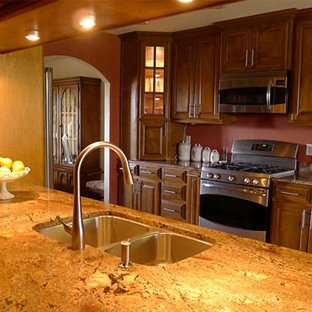Mid-sized southwestern enclosed kitchen appliance - Inspiration for a mid-sized southwestern galley enclosed kitchen remodel in Austin with a double-bowl sink, raised-panel cabinets, dark wood cabinets, granite countertops, brown backsplash and stainless steel appliances