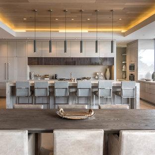 Modelo de cocina en L, contemporánea, abierta, con armarios con paneles lisos, puertas de armario grises, salpicadero verde, electrodomésticos con paneles, suelo de cemento, una isla y suelo gris