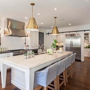 Bild på ett vintage kök, med en dubbel diskho, luckor med infälld panel, vita skåp, bänkskiva i koppar, vitt stänkskydd, stänkskydd i tunnelbanekakel, rostfria vitvaror, en köksö och mörkt trägolv