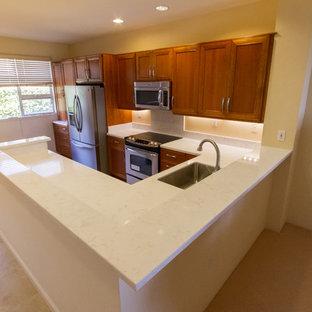 ハワイの中サイズのアジアンスタイルのおしゃれなキッチン (アンダーカウンターシンク、落し込みパネル扉のキャビネット、中間色木目調キャビネット、白いキッチンパネル、石スラブのキッチンパネル、シルバーの調理設備、アイランドなし、クオーツストーンカウンター、リノリウムの床、ベージュの床) の写真