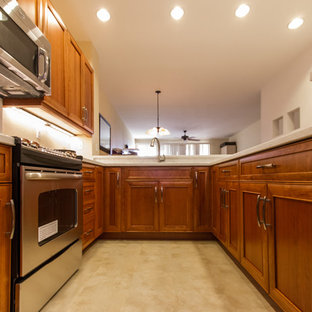Photo of a mid-sized asian u-shaped eat-in kitchen in Hawaii with an undermount sink, recessed-panel cabinets, medium wood cabinets, limestone benchtops, white splashback, stone slab splashback, stainless steel appliances, no island, laminate floors and beige floor.