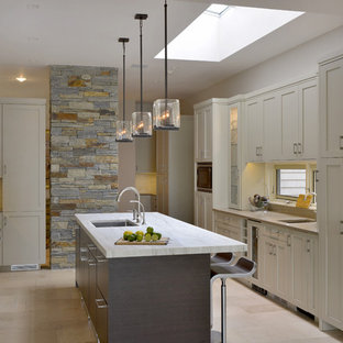 Large transitional eat-in kitchen remodeling - Large transitional u-shaped limestone floor eat-in kitchen photo in New York with an undermount sink, flat-panel cabinets, beige cabinets, stainless steel appliances, an island and granite countertops