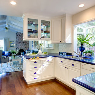 Photo of a small transitional galley open plan kitchen in San Francisco with an undermount sink, raised-panel cabinets, white cabinets, quartz benchtops, ceramic splashback, white splashback, stainless steel appliances, medium hardwood floors and blue benchtop.
