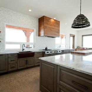 Foto på ett stort funkis grå kök, med en rustik diskho, luckor med upphöjd panel, skåp i mörkt trä, granitbänkskiva, grått stänkskydd, rostfria vitvaror, en köksö, brunt golv och terrazzogolv