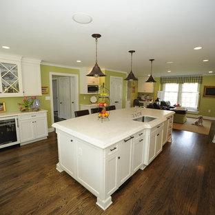 Offene, Mittelgroße Klassische Küche mit Triple-Waschtisch, Schrankfronten im Shaker-Stil, weißen Schränken, Quarzit-Arbeitsplatte, Elektrogeräten mit Frontblende, dunklem Holzboden und Kücheninsel in Baltimore