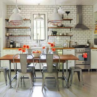 Landhausstil Wohnküche mit Landhausspüle, offenen Schränken, Arbeitsplatte aus Holz, Küchenrückwand in Weiß, Rückwand aus Metrofliesen, Küchengeräten aus Edelstahl und gebeiztem Holzboden in Atlanta