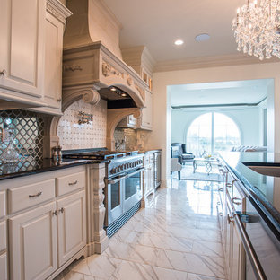 Design ideas for an expansive traditional single-wall open plan kitchen in New Orleans with a drop-in sink, louvered cabinets, white cabinets, granite benchtops, metallic splashback, mirror splashback, stainless steel appliances, ceramic floors, multiple islands and white floor.