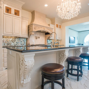 Inspiration for an expansive traditional single-wall open plan kitchen in New Orleans with a drop-in sink, louvered cabinets, white cabinets, granite benchtops, metallic splashback, mirror splashback, stainless steel appliances, ceramic floors, multiple islands and white floor.