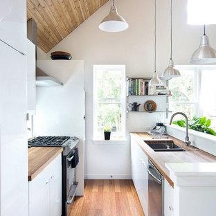 ロンドンの小さい北欧スタイルのおしゃれなII型キッチン (ダブルシンク、フラットパネル扉のキャビネット、白いキャビネット、木材カウンター、シルバーの調理設備の、無垢フローリング、アイランドなし) の写真