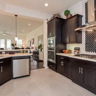 ヒューストンのトランジショナルスタイルのおしゃれなアイランドキッチン (ダブルシンク、シェーカースタイル扉のキャビネット、濃色木目調キャビネット、白いキッチンパネル、シルバーの調理設備の、淡色無垢フローリング) の写真