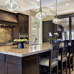 Inspiration for a mid-sized tropical u-shaped eat-in kitchen in Phoenix with an integrated sink, recessed-panel cabinets, dark wood cabinets, granite benchtops, multi-coloured splashback, stainless steel appliances, marble floors and with island.