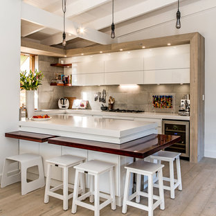Design ideas for a contemporary u-shaped kitchen in Adelaide with flat-panel cabinets, white cabinets, grey splashback, stainless steel appliances, light hardwood floors, a peninsula, beige floor and white benchtop.