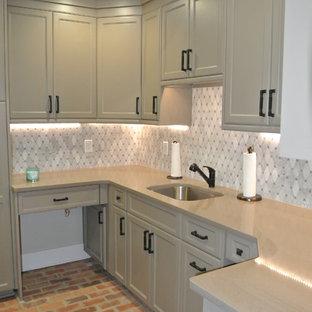アトランタの中サイズのトランジショナルスタイルのおしゃれなキッチン (アンダーカウンターシンク、シェーカースタイル扉のキャビネット、白いキャビネット、人工大理石カウンター、グレーのキッチンパネル、大理石の床、レンガの床、赤い床) の写真