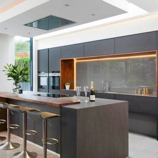 Photo of a large modern single-wall separate kitchen in DC Metro with a drop-in sink, flat-panel cabinets, black cabinets, wood benchtops, grey splashback, black appliances, porcelain floors, with island, beige floor, glass sheet splashback and brown benchtop.