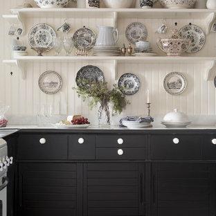 Idées déco pour une cuisine campagne avec des portes de placard noires, un électroménager blanc et un sol blanc.