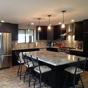 フェニックスの中くらいのサンタフェスタイルのおしゃれなキッチン (ダブルシンク、シェーカースタイル扉のキャビネット、濃色木目調キャビネット、御影石カウンター、マルチカラーのキッチンパネル、ガラスタイルのキッチンパネル、シルバーの調理設備、ライムストーンの床、ベージュの床) の写真
