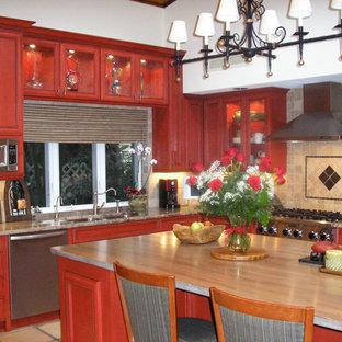 マイアミの中サイズの地中海スタイルのおしゃれなキッチン (ダブルシンク、ガラス扉のキャビネット、赤いキャビネット、木材カウンター、マルチカラーのキッチンパネル、モザイクタイルのキッチンパネル、シルバーの調理設備の、セラミックタイルの床) の写真