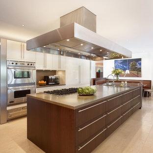 Foto di una cucina minimal di medie dimensioni con lavello a doppia vasca, ante a filo, ante bianche, top alla veneziana, paraspruzzi marrone, elettrodomestici in acciaio inossidabile, pavimento in travertino e isola
