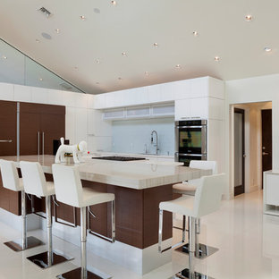 Bild på ett stort funkis kök, med släta luckor, vita skåp, rostfria vitvaror, en köksö, vitt golv, en undermonterad diskho, marmorbänkskiva, vitt stänkskydd, stänkskydd i keramik och klinkergolv i porslin