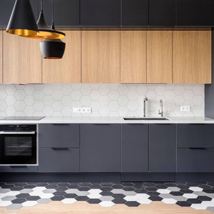 Inspiration for a mid-sized contemporary l-shaped separate kitchen in Toronto with an undermount sink, flat-panel cabinets, white splashback, light wood cabinets, quartz benchtops, porcelain splashback, black appliances, porcelain floors, with island, multi-coloured floor and grey benchtop.